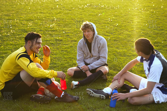 Young soccer players relaxing on soccer field