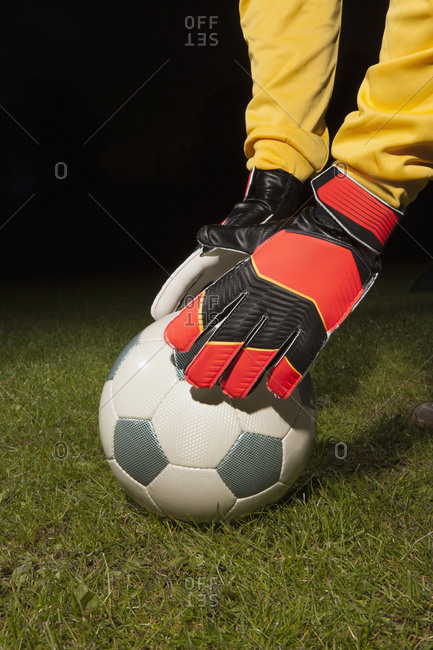 Young male goalie placing soccer ball on field