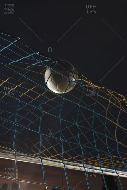 Low angle view soccer ball in goal at night