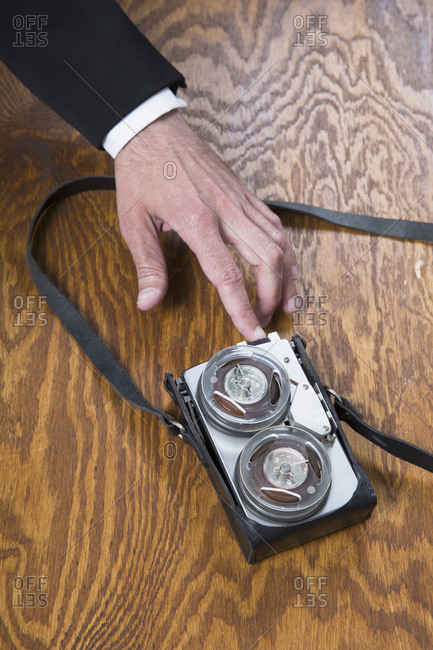 Businessman using old-fashioned tape recorder on wooden table