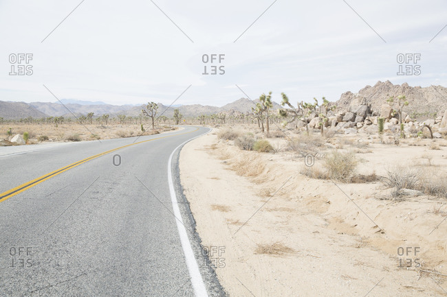 Road passing through arid landscape against sky