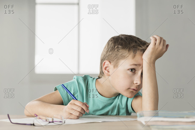 Bored boy with hand on forehead doing homework at home