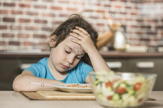 Sad girl with head in hand while having breakfast at table