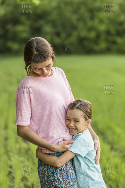 Smiling girl hugging mother on field