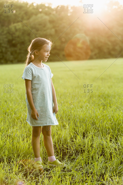 Happy girl standing on grassy field