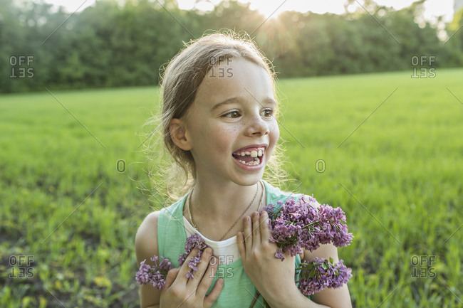 Cheerful girl holding purple flowers on field