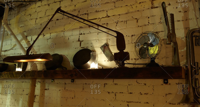 Arrangement of lamp and antique objects with candles on shelf against brick wall