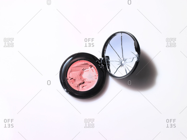 Shattered mirror in a compact of pink cream blush