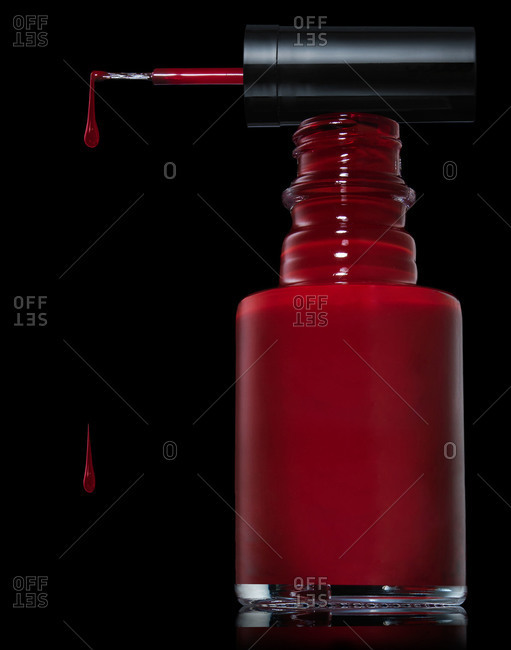Red nail polish in a bottle with drips falling off the brush applicator