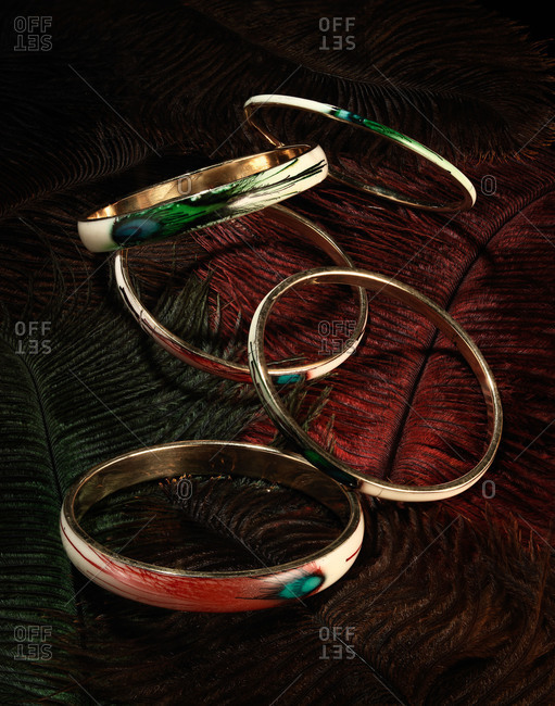 Bracelets with peacock feather designs rest on a bed of feathers