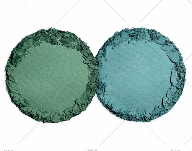 Green and blue rounds of powdered eye shadow with crushed edges