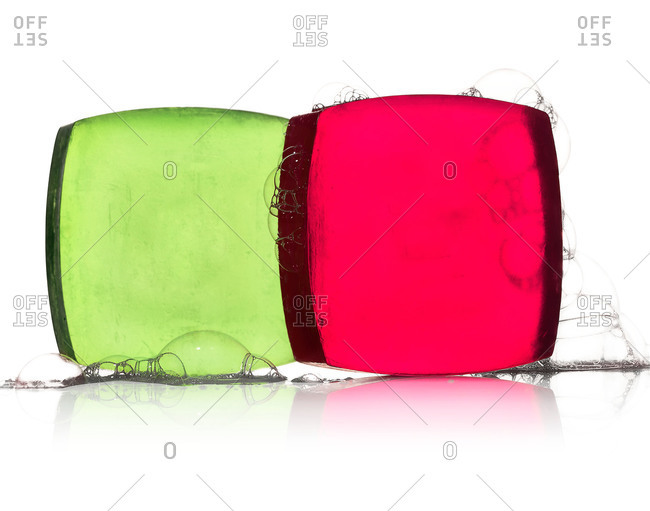 Two square bars of green and pink glycerin soap