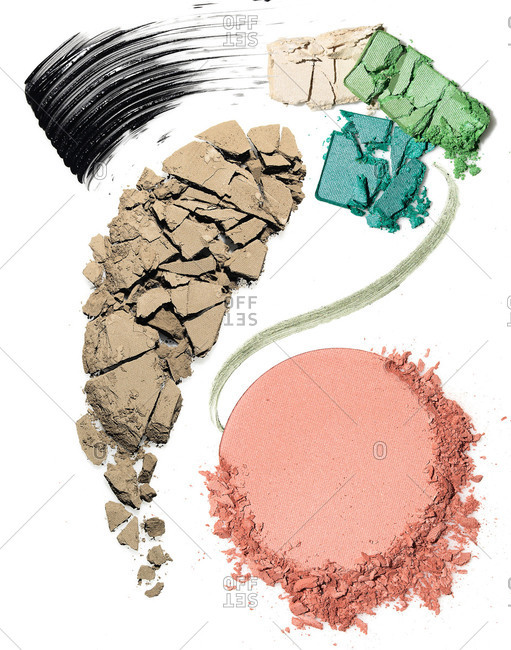Different types of makeup smeared and crushed on a white background