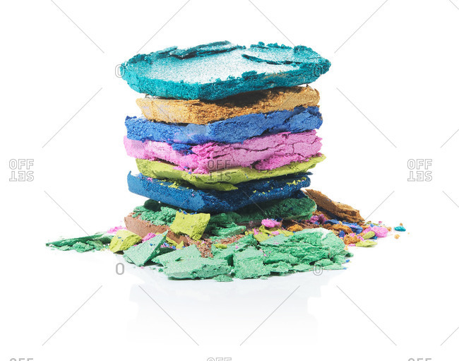 Stack of colorful eye shadow hues on white background