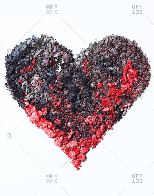 Red and black crumbled powdered eye shadow arranged in a heart shape