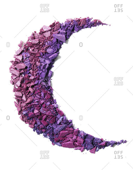 Hues of purple eye shadow powder formed in the shape of a crescent moon