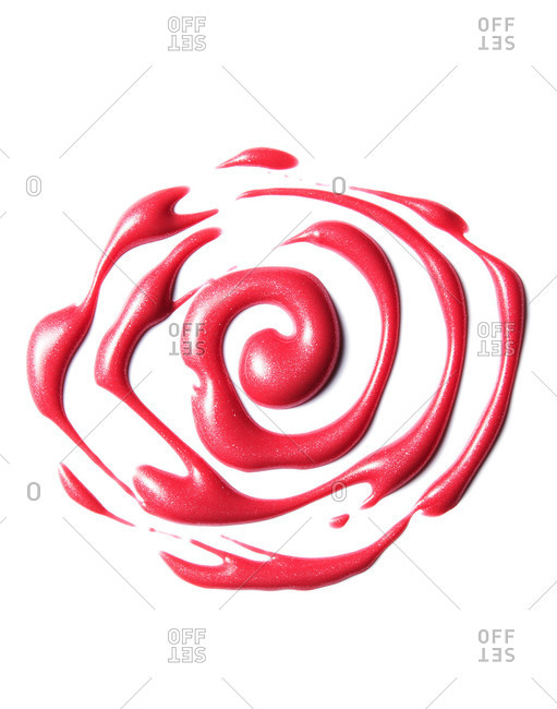 Spiral of pink shimmery lip gloss on white background