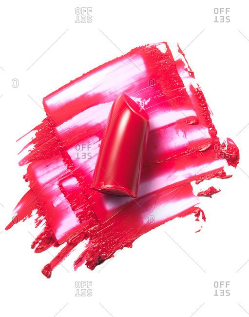 Glossy fuchsia lipstick smeared on white background