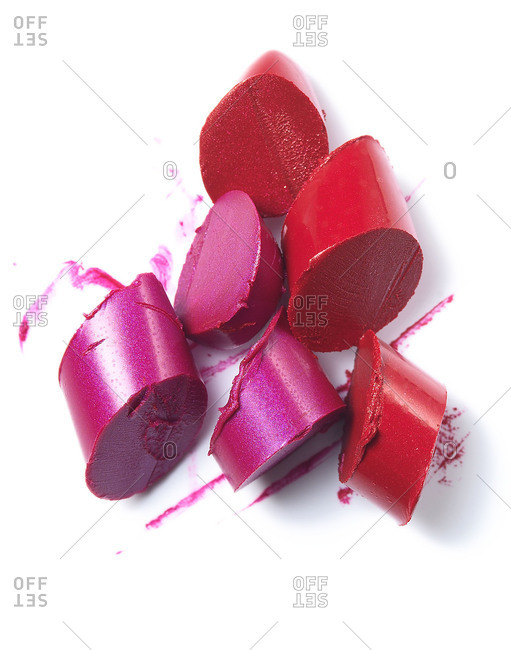 Slices of red and purple lipstick on white background