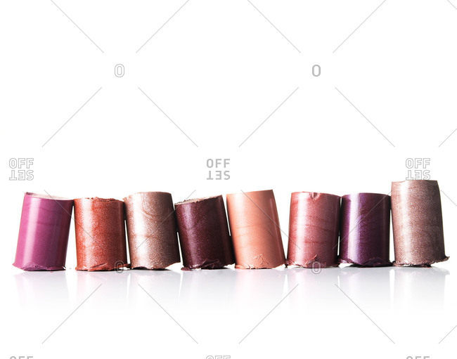 Row of shimmery cylinders of lipstick on white background