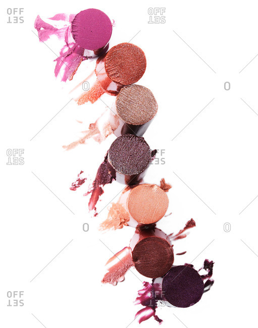 Overhead view of sliced rounds of lipstick on white background