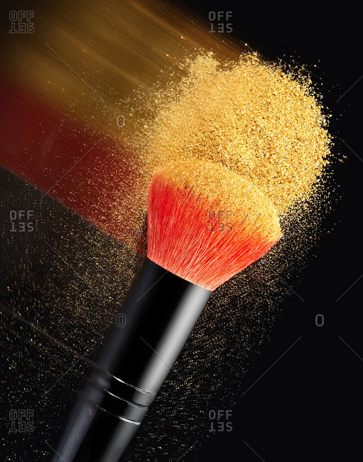 Blurred streak of gold makeup on a brush