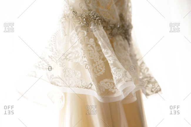 38d728d737b A lacy wedding dress hangs in a window stock photo - OFFSET