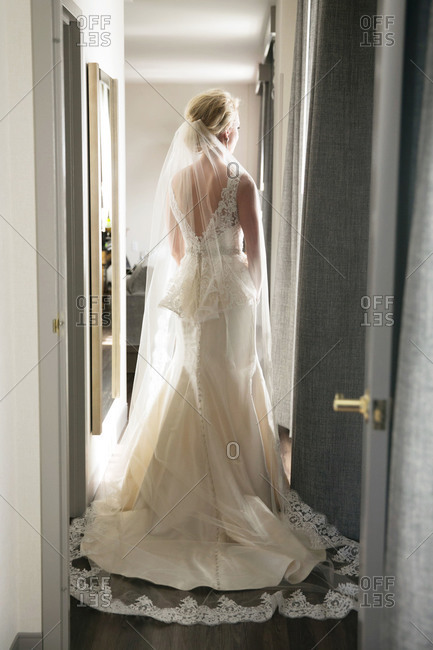 A bride stands in a hallway