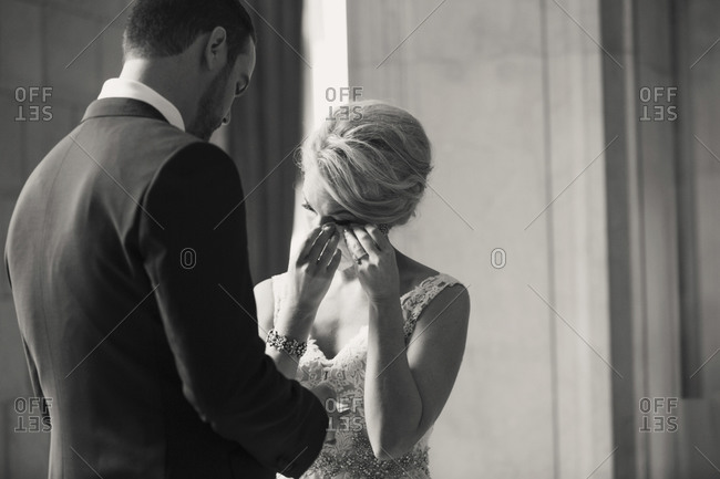A bride dries her eyes with her new husband