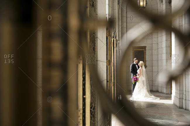 A bride and groom stand  in the entrance to a hotel