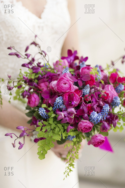A bride holds her bouquet of bright purple flowers