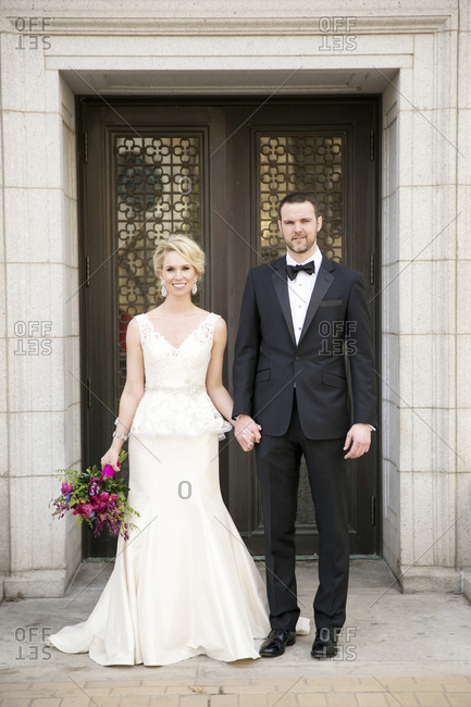 A bride and groom hold hands in front of a doorway