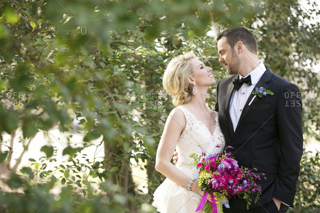 A bride and groom smile at each other in a wooded area