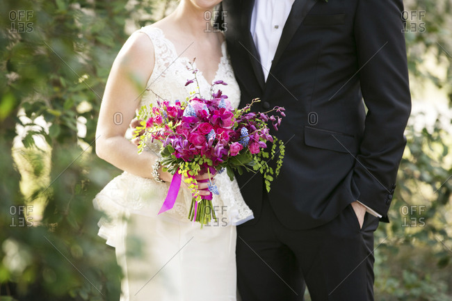 A bride and groom stand together a wooded area