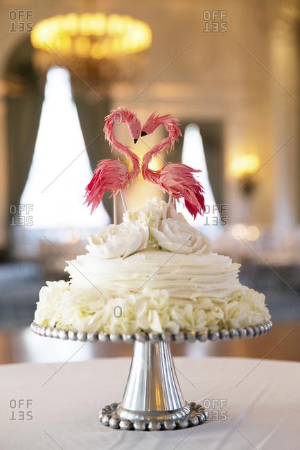 Two flamingos decorate a wedding cake