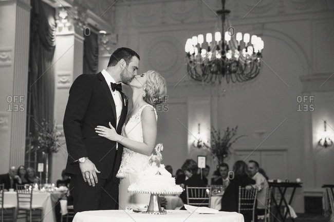 A bride and groom kiss in front of their wedding cake