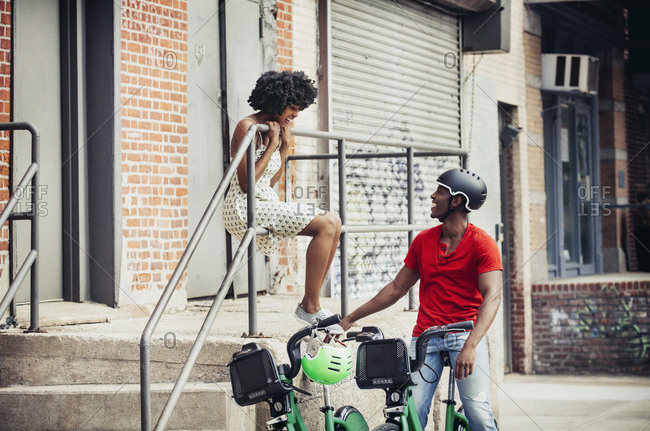 Young couple on a bicycle ride sitting and laughing