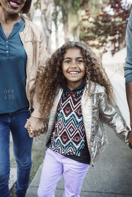 Little girl walking down a sidewalk holding her parents' hands