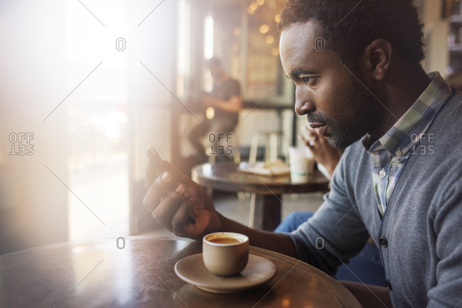 Man looking at his phone in a coffee shop