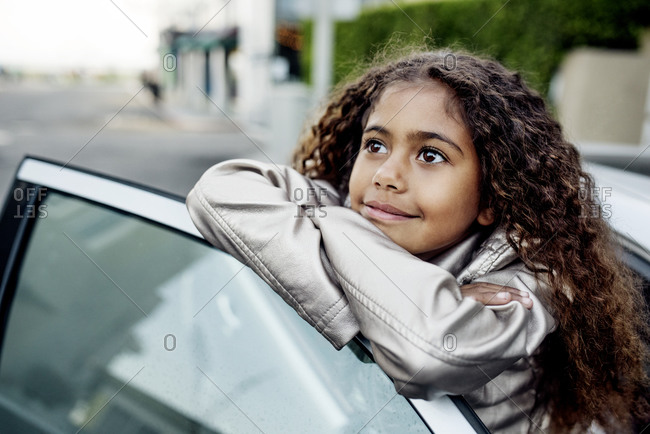 Little girl resting her head on her arms atop a car door