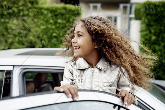 Little girl standing and holding the top of a car door