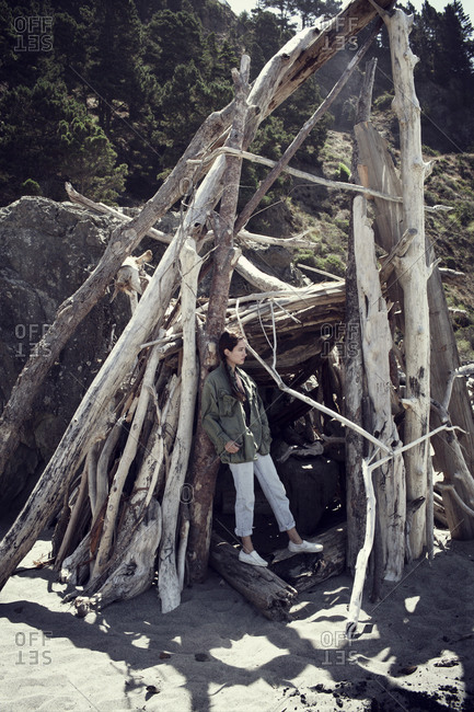 Woman standing at the entrance to a shelter made of logs