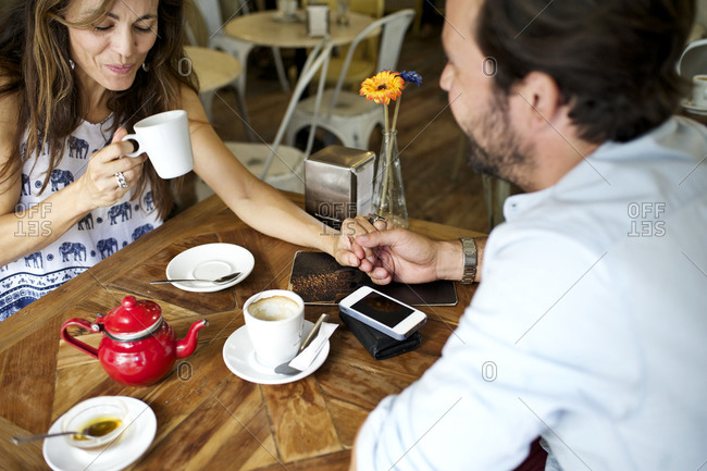 Couple at a coffee shop sitting together and holding hands