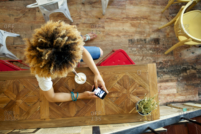 Young woman at a coffee bar checking her phone