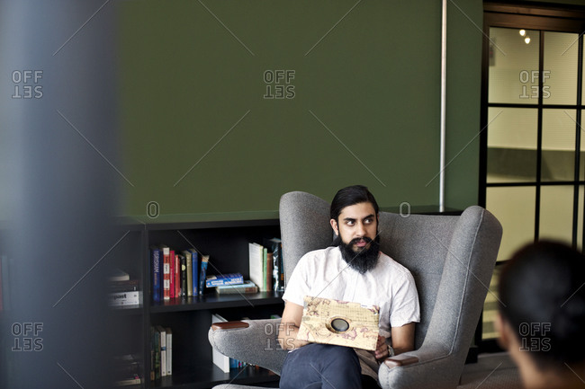 Young man sitting in an armchair with a tablet