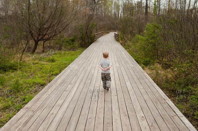 Little boy walking on a boardwalk through the woods