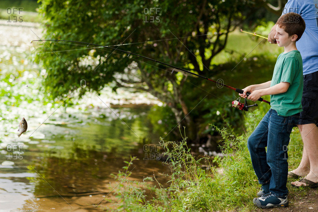 Young boy and father fishing at a lake