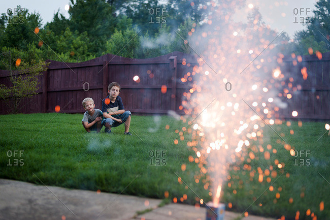Brothers watching backyard fireworks