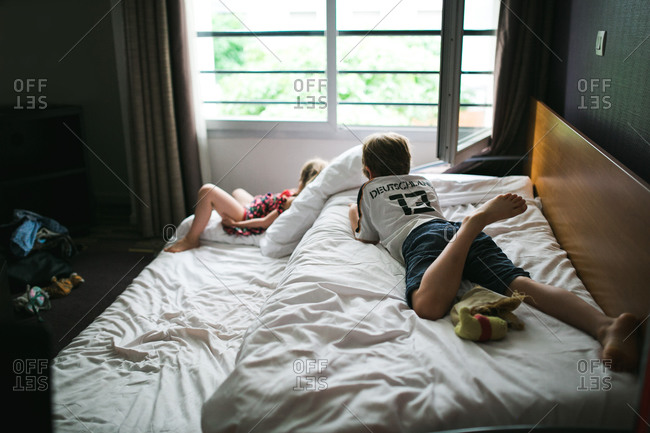 A boy and his little sister relax on hotel beds