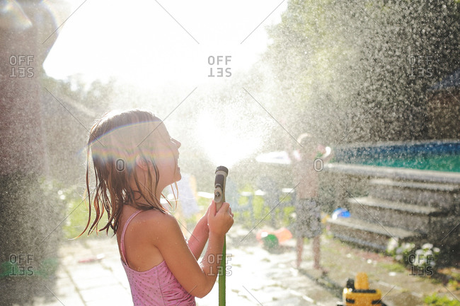 A girl sprays water from a hose in her backyard